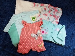 An assortment of special Keepsake baby clothing used to make the bearloom.
