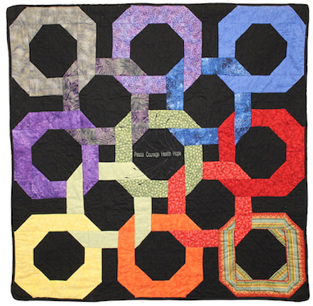 A black memory quilt with 13 interlocking circles the color of the rainbow, representing a stage of cancer recovery.