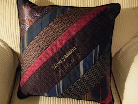 An Heirloom memorial pillow made from red and black ties with red embroidery.  The design is diagonal strips of ties that stretch to bottom left to top right hand corner.