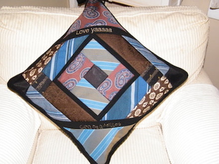 An heirloom memorial pillow made from ties that are blue and brown.  It is a version of a log cabin piecing design. Custom embroidery is done in gold.