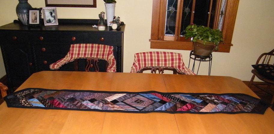 Memory table runner made from ties and embroidered signatures