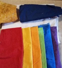 Pieces of fabric, one each in colors of the rainbow, folded and placed in order.