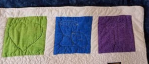 3 of the top color squares with their quilting design.  Green with a heart, blue with a chalice and loaf of bread and purple with a cross.