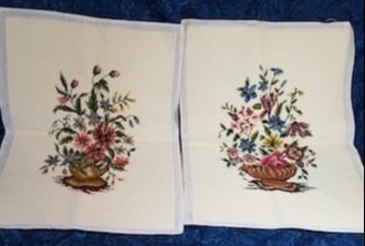 two needlepoint pieces with ivory backgrounds and blue and pink floral motifs