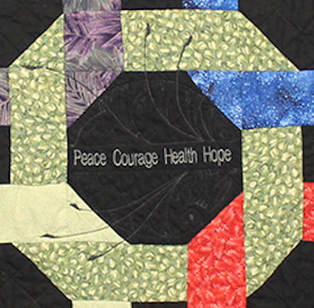 The center of the memory quilt is embroidered with a design with the words, Peace, Courage, Health and Hope.