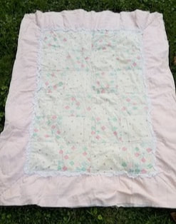 A vintage quilt that is pink, blue, white and green and worn with age.