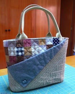 A quilted bag with handles.  The pocket in the from is made by finding down the fabric at an angle.  The background fabric is multi colored patchwork