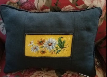 front of a black linen memory pillow with a  piece of the vintage bell pull inserted in the middle