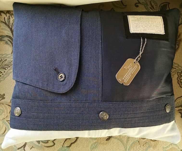 An heirloom memorial pillow made from a military uniform using a trench coat flap, the lining, information tag, dog tag, dress shirt and buttons.