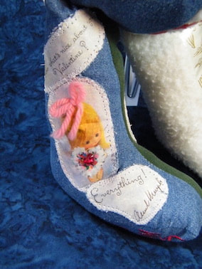 close up of a paper valentine sewn to the memory bunny's leg.