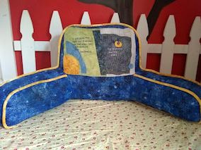 The blue pillow with arms with yellow pipping and the appliquéd design on the back, sits on her bed with her white picket fence wall design behind it.