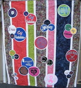 A unique memory t-shirt  quilt -  Strips of white and batik fabric topped with  t-shirts cut into circles and mounted on white circles.
