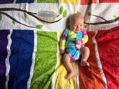 Adorable baby named Robin on rainbow quilt with robin's nest