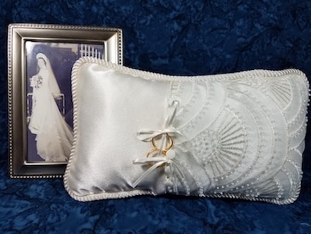 A vintage picture of a woman in a wedding dress behind a keepsake ring bearer pillow made of wedding dress materials.