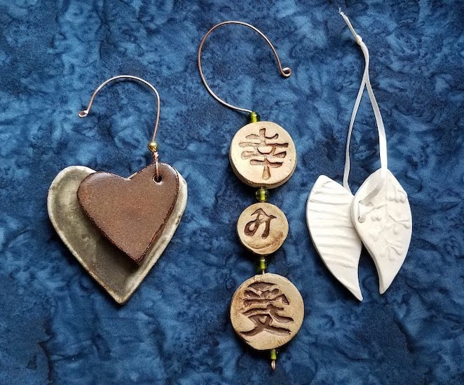Set of three unique ornaments made in honor of family weddings.  1. two over lapping clay hearts in burgundy and grey hung from then right side of the two hearts 2. 3 small clay disks imprinted with a stamps, 3. two embossed porcelain leaves joined with ribbon at the facing edges.